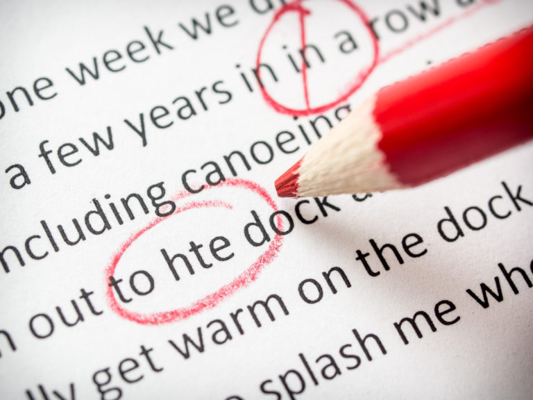 A typed document showing red proofreading and copy-editing marks with a red pencil at the ready to catch more errors